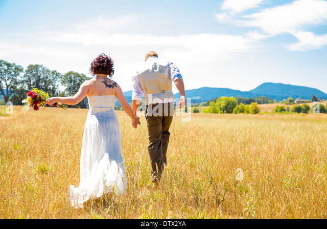 Bride and groom walking together on their wedding day through a field in Oregon. - Stock-Bilder