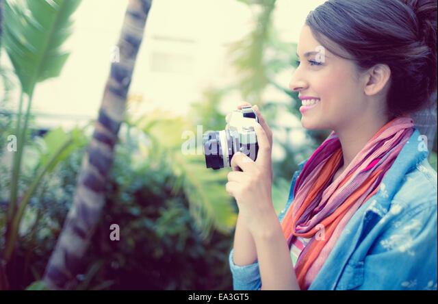 Smiling brunette taking a photo - Stock-Bilder