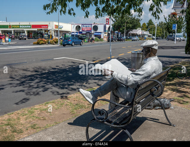 Barry - statue of a Kiwi bloke sitting reading a newspaper on a bench, main road katitkati town, Bay of Plenty New - Stock Image