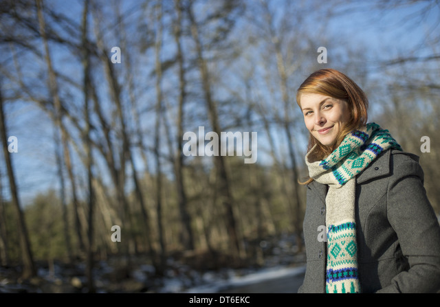 A young woman in a woodland on a winter day.  Wearing a bright knitted patterned scarf. - Stock Image