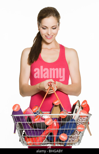 Woman with basket full of sale shoes - Stock Image