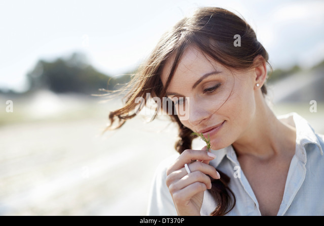 A young woman with windblown hair with a small green sprig of plant material in her hand - Stock Image