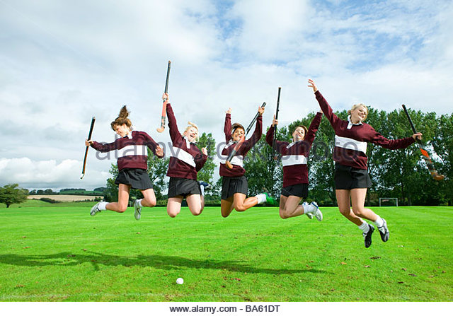 Teenage girl hockey team jumping on field - Stock Image