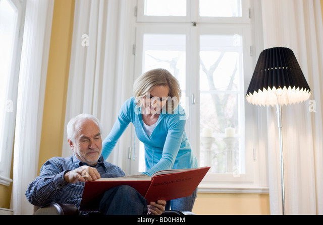 old father and daughter reading book - Stock Image
