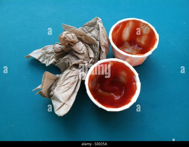 Two used containers of ketchup and a crumpled napkin - Stock Image