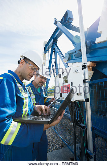 Male workers with laptop at oil well - Stock-Bilder