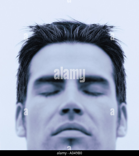 Close up portrait of young man  eyes closed  blue toned - Stock Image