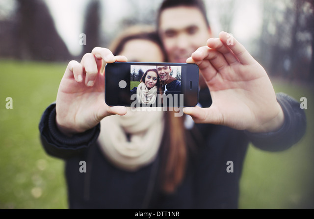 Mixed race young boy and girl making a funny face while taking a self portrait with mobile phone. Cute young couple. - Stock Image