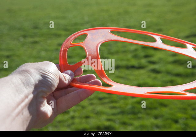 hand holding a rubber soft frisbee green grass - Stock Image