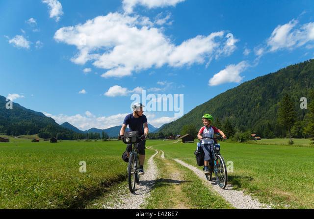 Father and son cycling through Jachenau, Bavaria, Germany - Stock Image