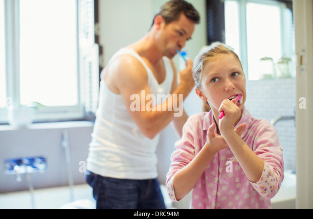 Father and daughter brushing teeth in bathroom - Stock-Bilder