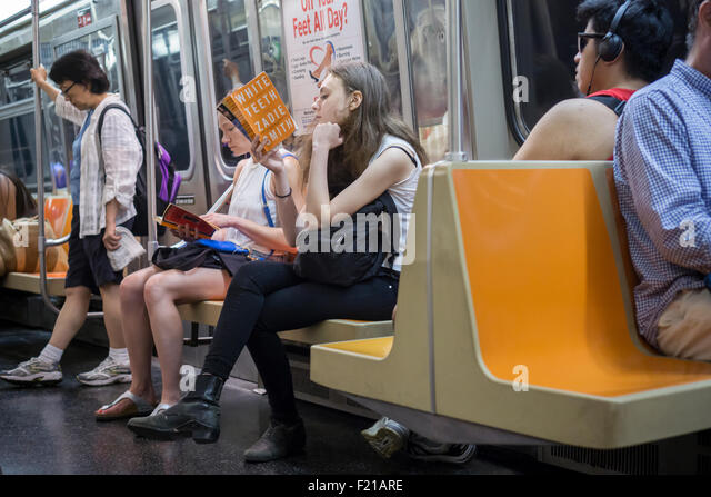 A woman reads a hardcover book on subway train in New York on Saturday, September 5, 2015. (© Richard b. Levine) - Stock Image