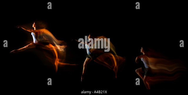 dancer jumping through the air showing motion as trails of light impact - Stock Image