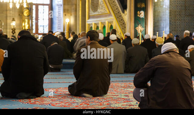 ISTANBUL, TURKEY - 22 MARCH, 2013: Muslim men praying in Yeni Cami (New Mosque) interior. New Mosque is located - Stock Image