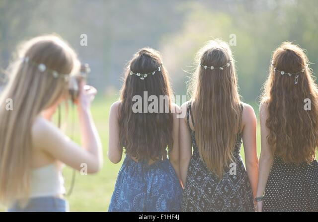 Rear view of teenage girl photographing friends wearing daisy chain headdresses in park - Stock Image