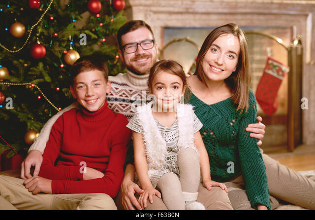 Happy family of four looking at camera on Christmas evening - Stock Image