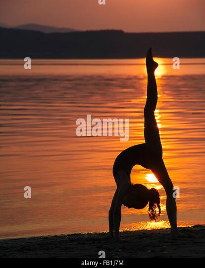 Side view of girl in silhouette by ocean at sunset bending over backwards leg raised doing the splits - Stock Image