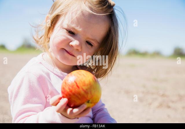 Portrait of girl (2-3) holding apple - Stock-Bilder