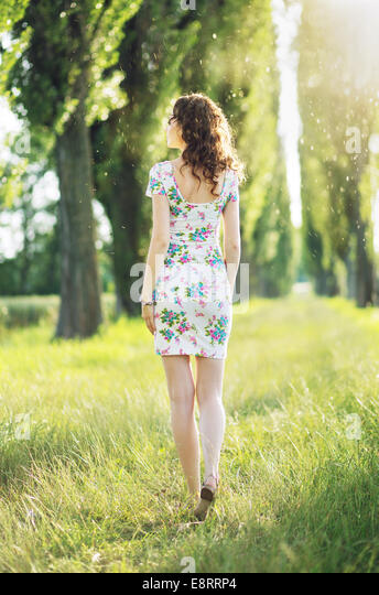 Picture presenting the lady walking among the trees - Stock Image