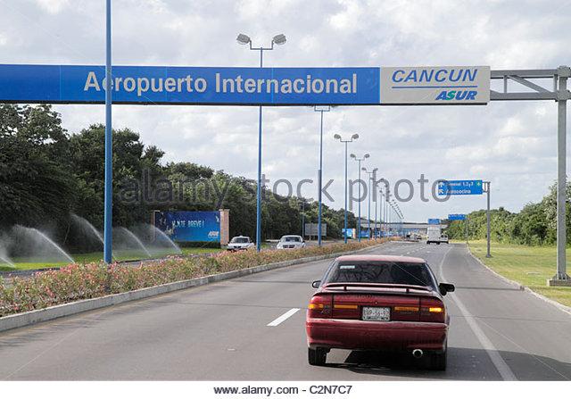 Cancun Mexico Yucatán Peninsula Quintana Roo Cancun International Airport entrance roadway sign median car - Stock Image