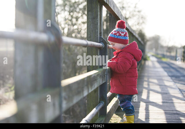 Boy standing on a bridge looking down at river - Stock Image