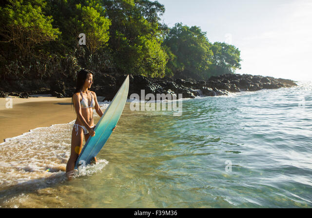 Mid adult woman on the beach standing in the surf holding her board, Bali, Indonesia - Stock Image