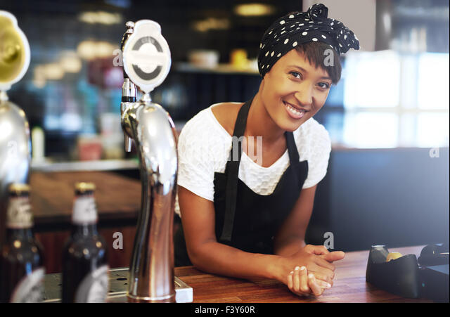 Attractive young African American small business owner dressed in a head scarf and apron leaning on the counter - Stock Image