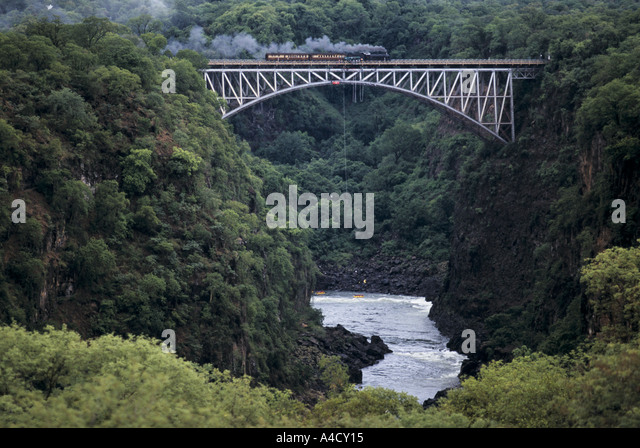 A steam train travelling between Bulawayo and  Victoria Falls, Zimbabwe, crossing a bridge, Africa - Stock Image