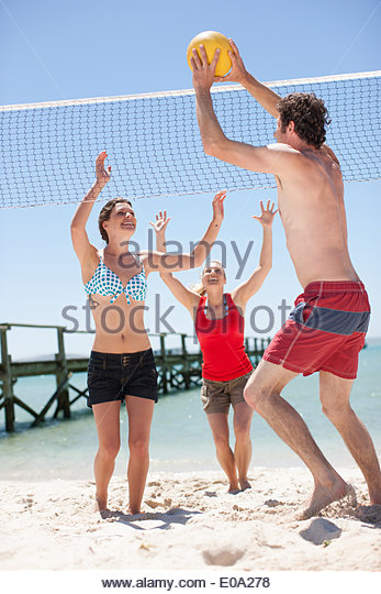 Friends playing volleyball on beach - Stock Image