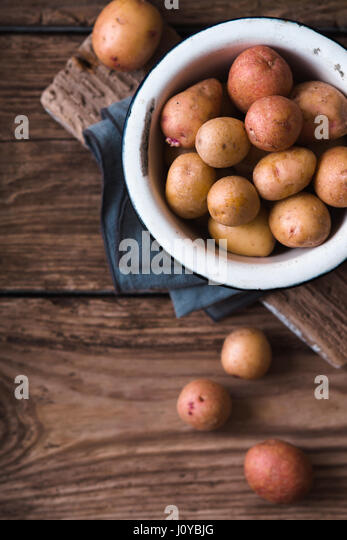 Raw potatoes in the metal bowl on the wooden table top view - Stock Image
