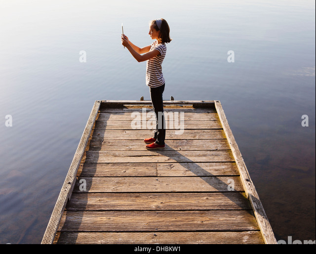 A young girl holding a digital tablet in front of her, standing on a wooden dock over the water. - Stock Image