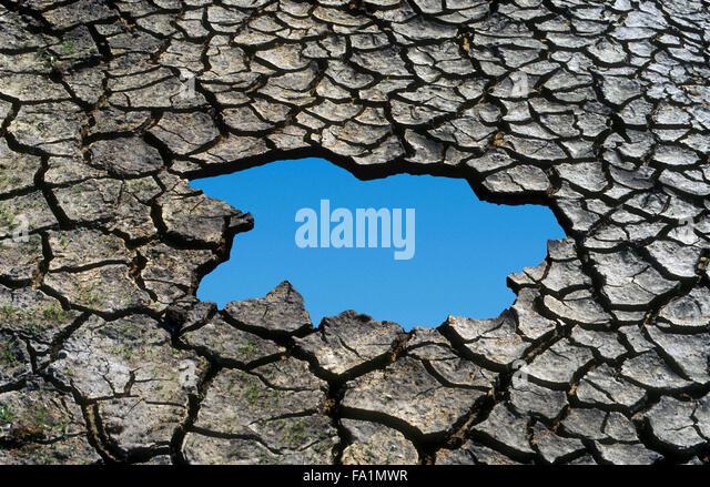 Blue sky thinking through cracked mud - Stock Image