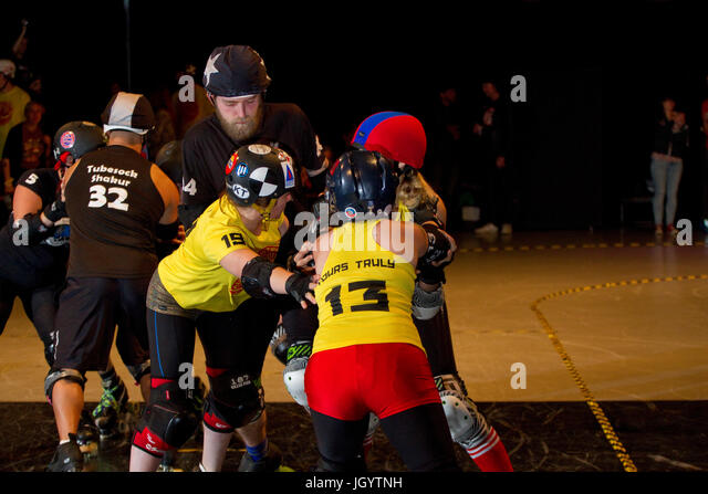 Men and women together competing at roller derby - Stock Image