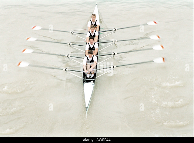 Four teenage boys rowing crew in boat, high angle view - Stock Image