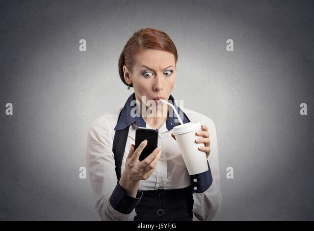 Closeup portrait surprised business woman reading breaking news on smart phone holding mobile drinking soda coffee - Stock Image