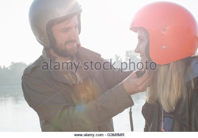Man helping woman put on crash helmet, smiling - Stock Image