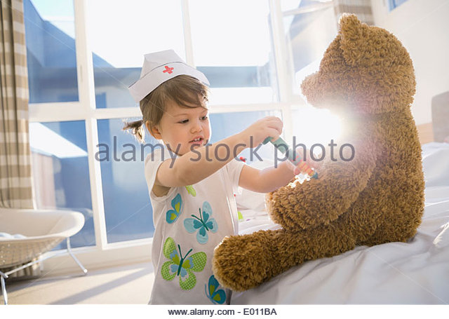 Girl in costume playing nurse to teddy bear - Stock Image
