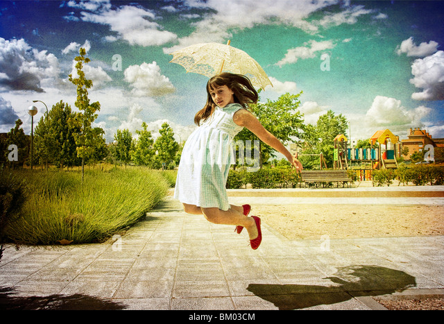 A young girl wearing a white summer dress with red shoes holding a sun shade jumping into the air - Stock Image