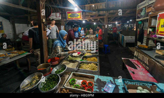 Indonesian woman taking food at booth, Food Market, Yogyakarta, Java, Indonesia - Stock Image
