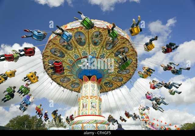 Families enjoying an amusement park ride at a carnival - Stock Image