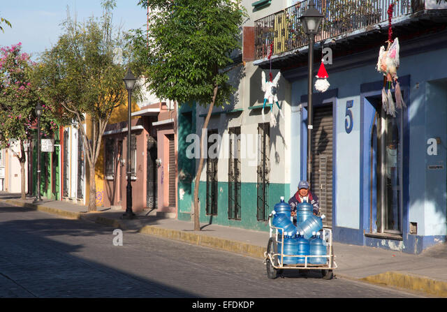 Oaxaca, Mexico - A man delivers bottled water with a hand cart. - Stock Image