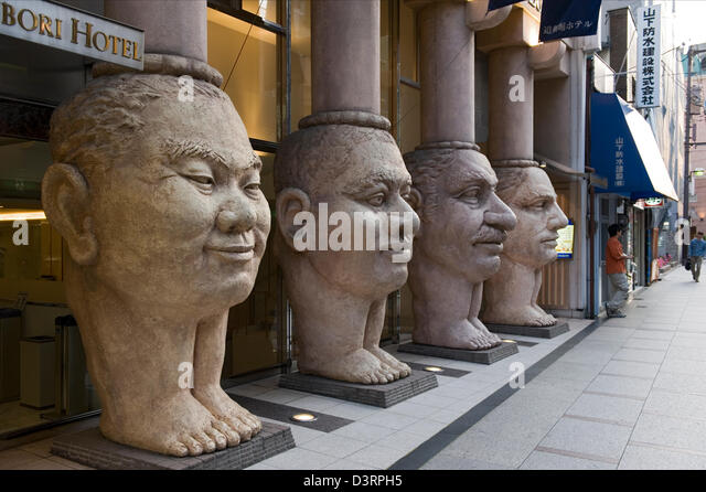 Unique artistic column figure heads at Dotonbori Hotel in Namba, Osaka depict Asian, African, Arabic and Western - Stock-Bilder