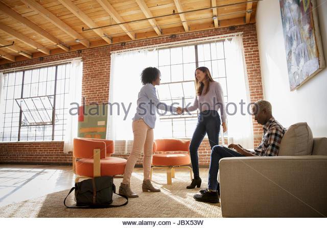 Two women shaking hands in bare office, man sitting on sofa using laptop - Stock-Bilder