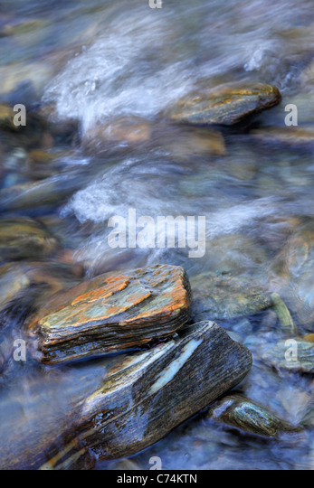 Water flowing amidst the colorful rocks of the Haast River in Haast Pass, New Zealand - Stock Image