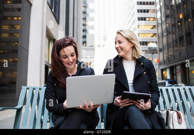 Female colleagues using laptop while sitting on bench in city - Stock-Bilder