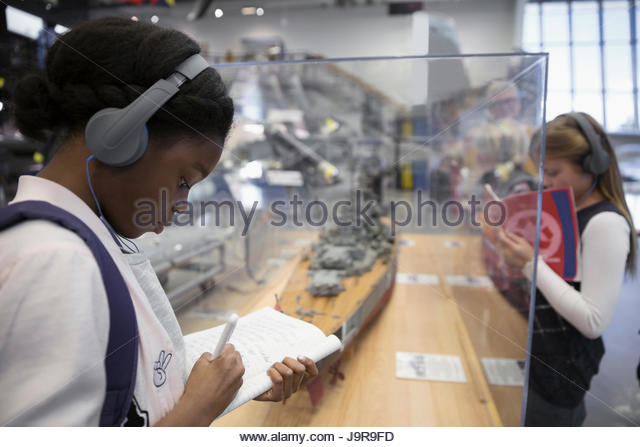 Girl students wearing headphones, taking notes at model Naval ship exhibit on field trip in war museum - Stock-Bilder