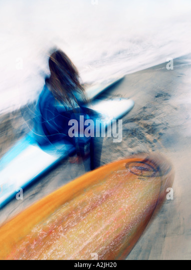 Female surfer sitting on the beach on her surf board. The Image is portrait format and features movement. - Stock Image