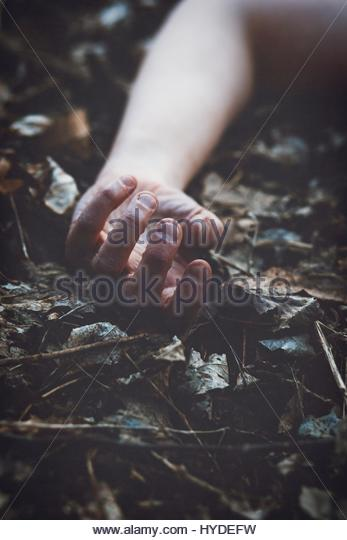 A woman's hand laying on the ground - Stock Image