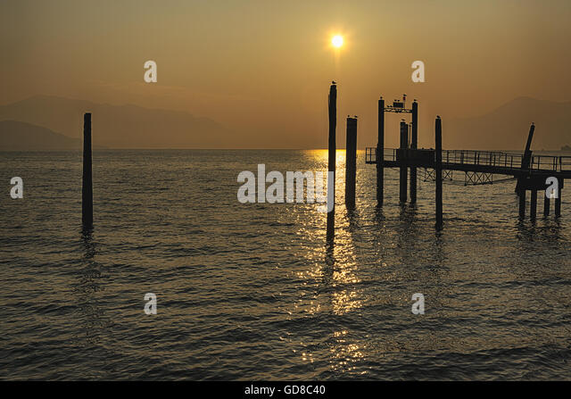 Pier at the sunset on the Major Lake in a wonderful contest with mountains at the horizon - Stock Image