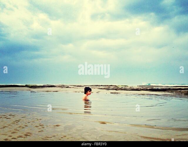 Shirtless Boy Swimming In Sea - Stock Image